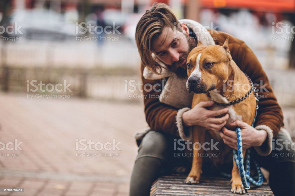 Man enjoying outdoors with dog on the bench