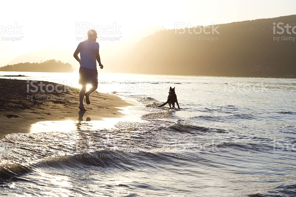 Man and Dog Running on the Beach stock photo