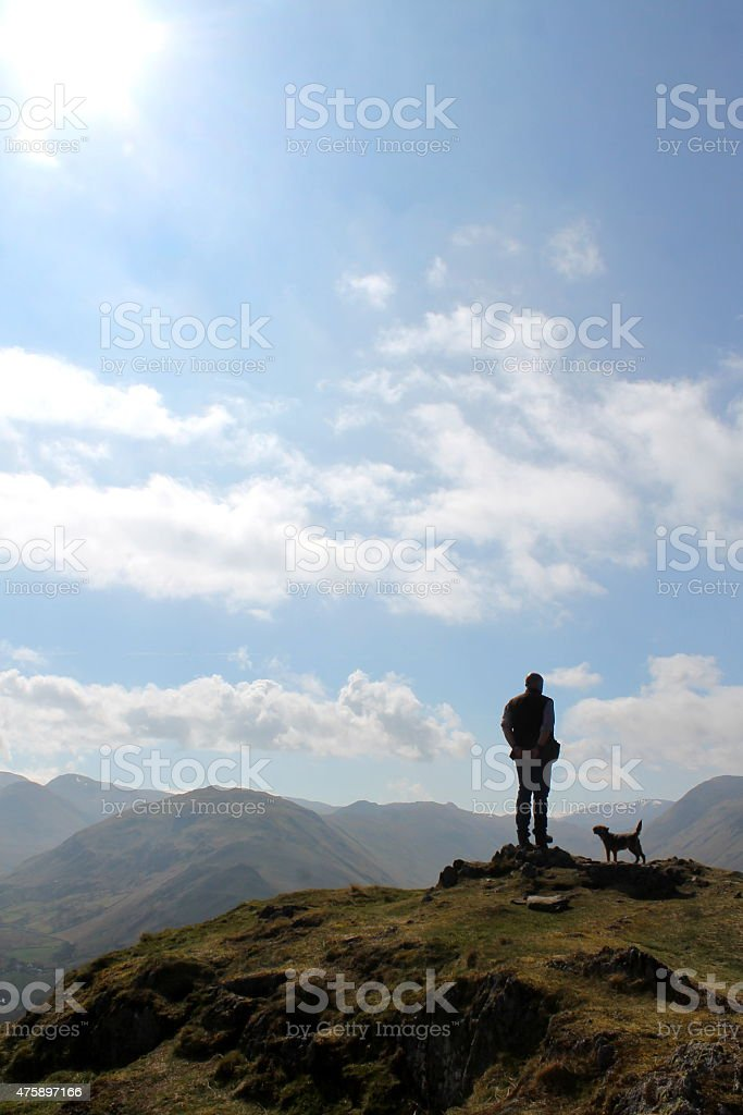 Man and dog silhouette on Hallin Fell, Lake District, UK stock photo