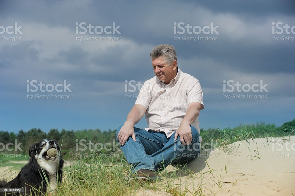 Man and dog, sitting/lying in sand dunes royalty-free stock photo