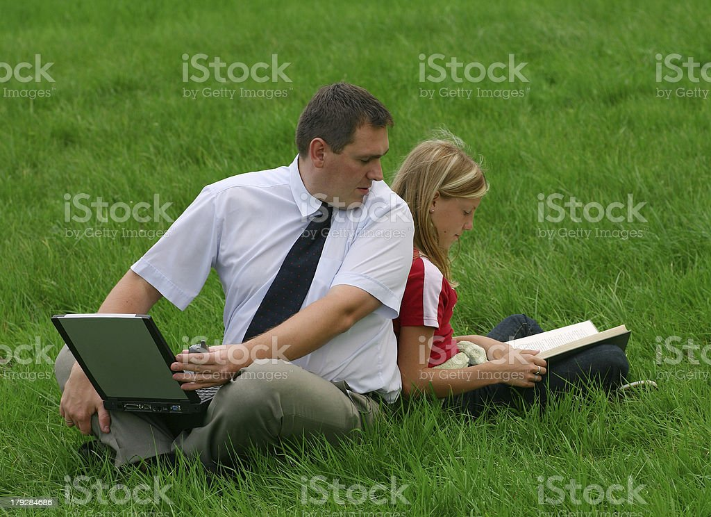 Man and girl sitting in the grass royalty-free stock photo