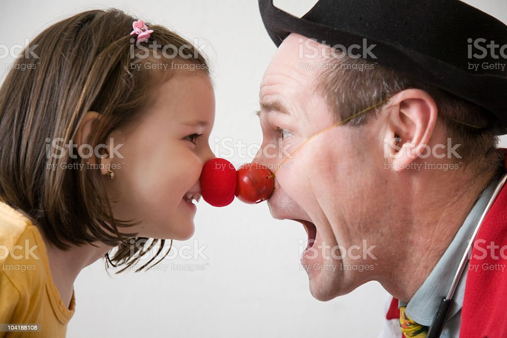 Man and girl wearing clown noses and touching their noses stock photo