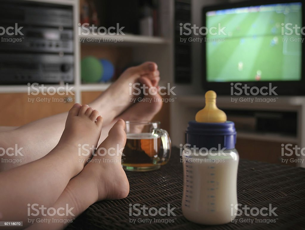 A man and his baby son watching football stock photo