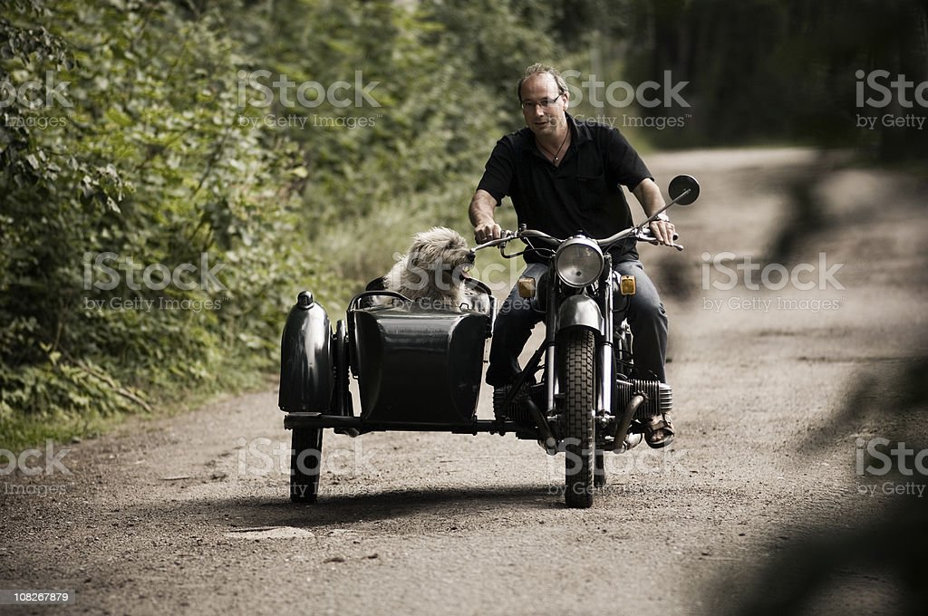 Man and his dog on motorcycle stock photo