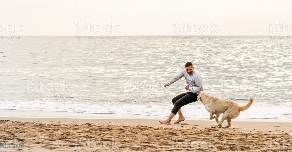 Man and his dog running a beach stock photo