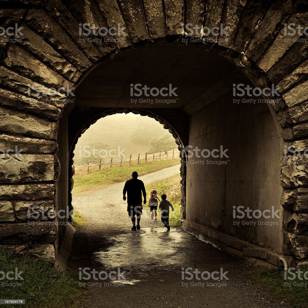 man and his kids walking thru a tunnel stock photo
