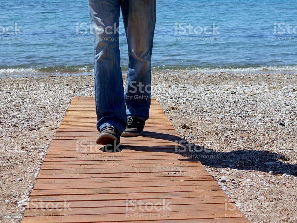 Man and his shadow leaves the beach stock photo