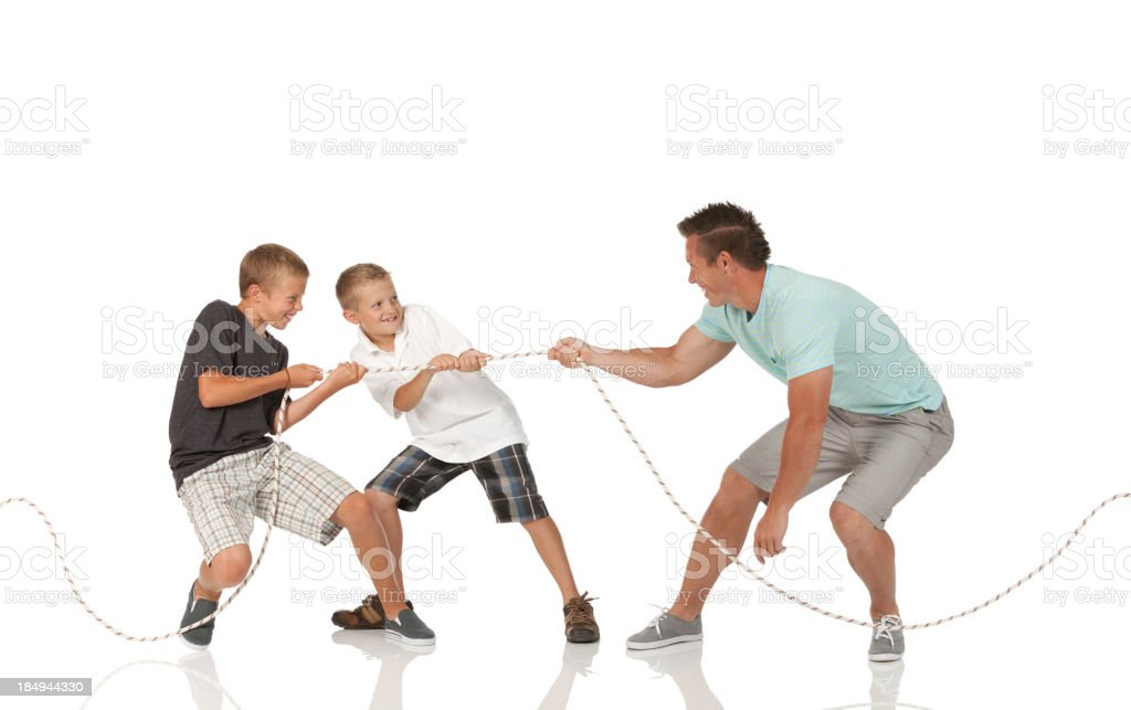 Man and his two sons playing tug-of-war royalty-free stock photo