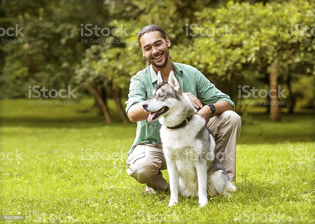 Man and Husky dog walk in the park. stock photo