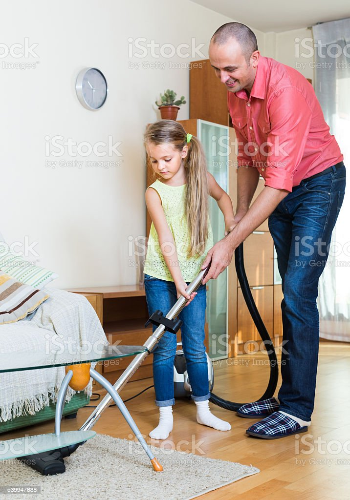 Man and little girl vacuuming at home stock photo
