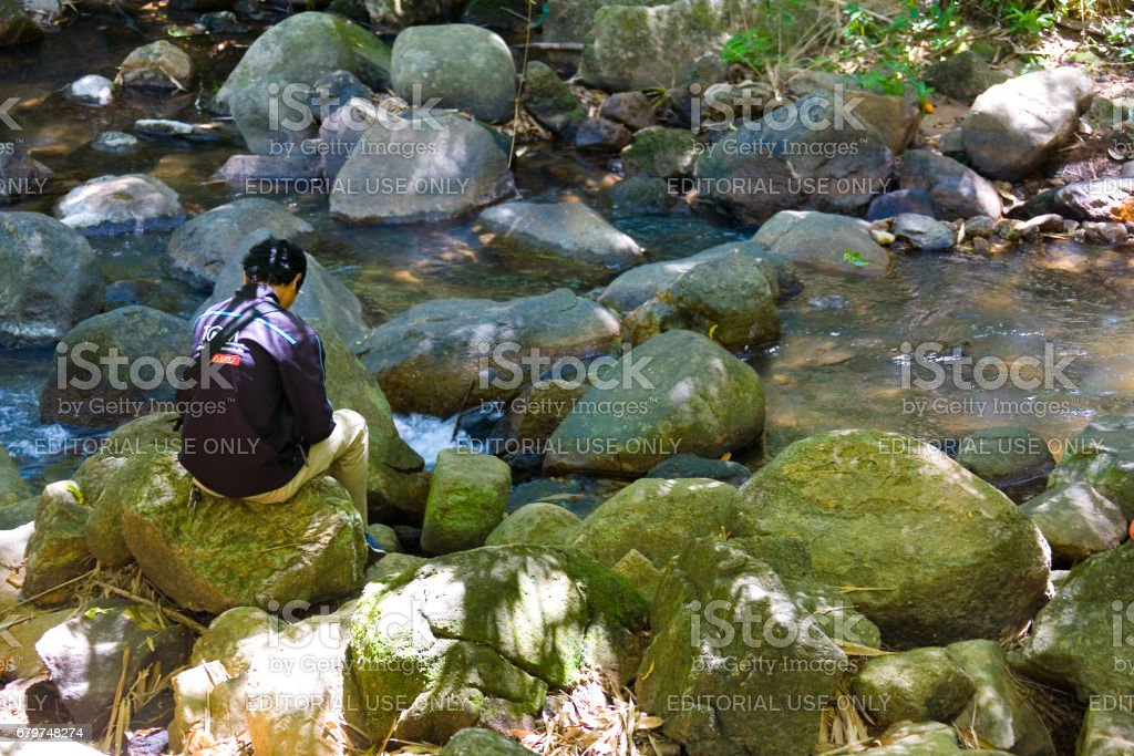 Man and nature. A man sits on rocks in a picturesque place by a mountain river. stock photo