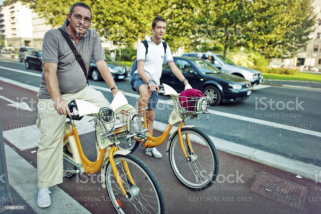 Man and teenager cycling in Milan royalty-free stock photo