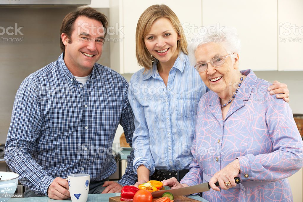 Man and two woman smiling at camera while cutting vegetables royalty-free stock photo