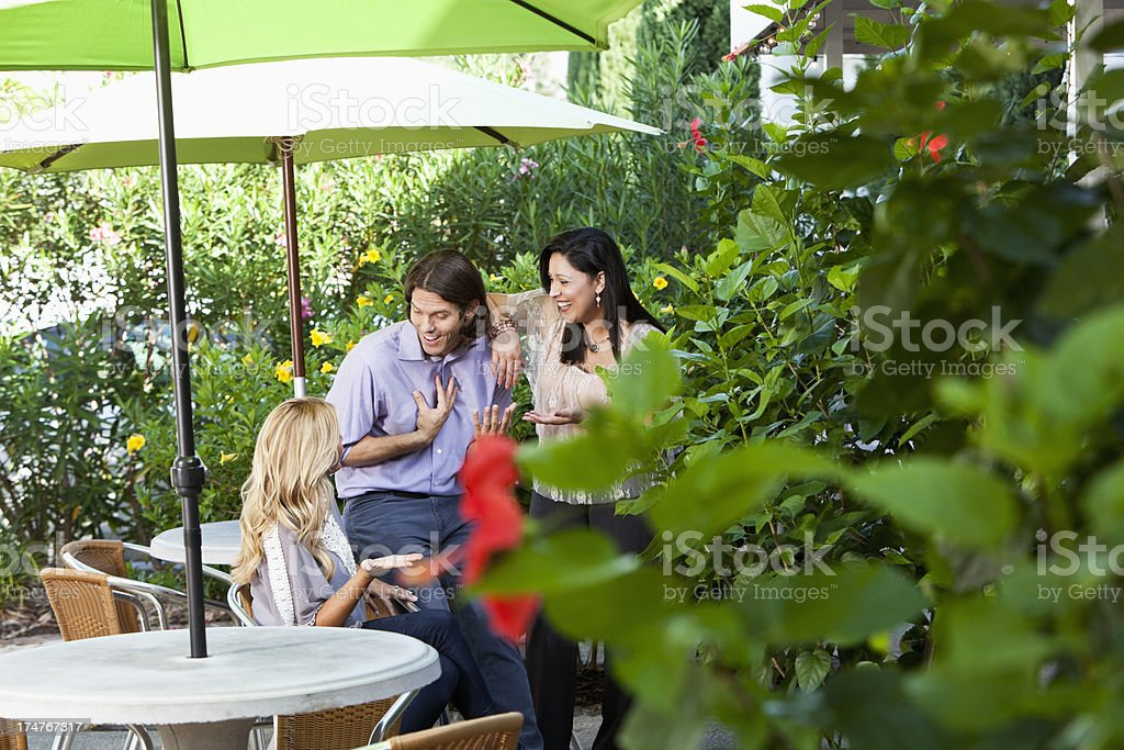 Man and two women talking on patio stock photo