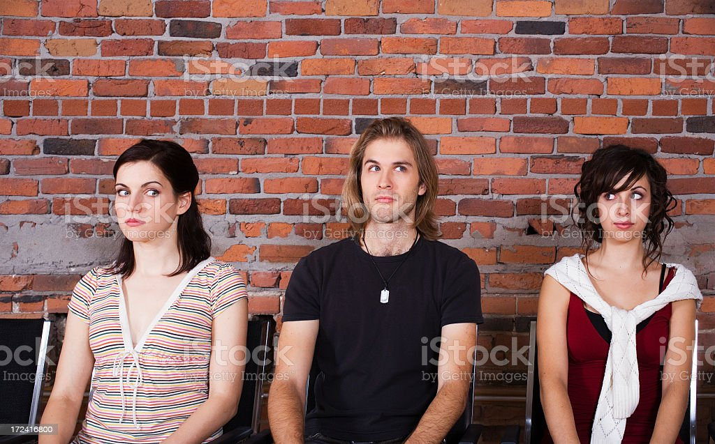 A man and two women waiting together stock photo