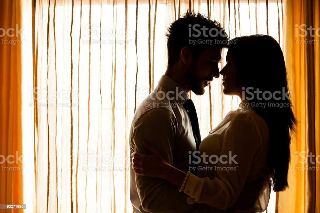 Man and woman about to kiss in front of window stock photo