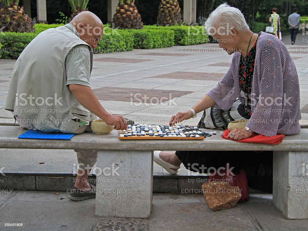 man and woman are playing go in the park stock photo