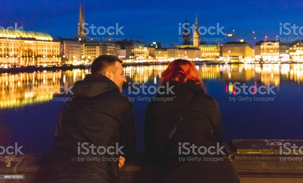 Man and woman are talking near the Alster lake. stock photo