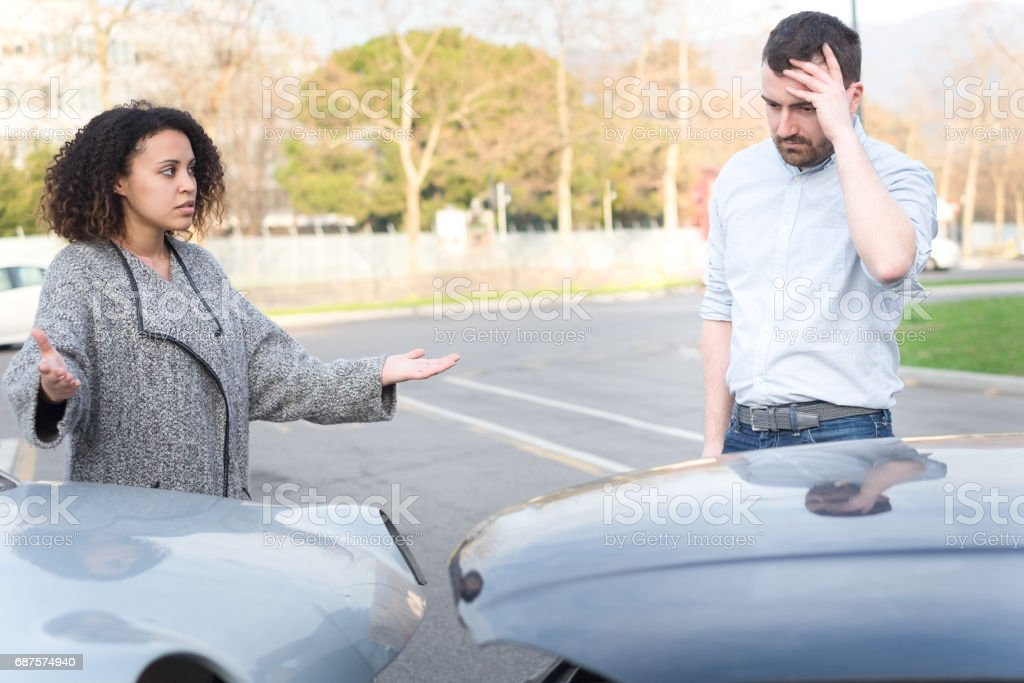 Man and woman arguing after bad car crash stock photo