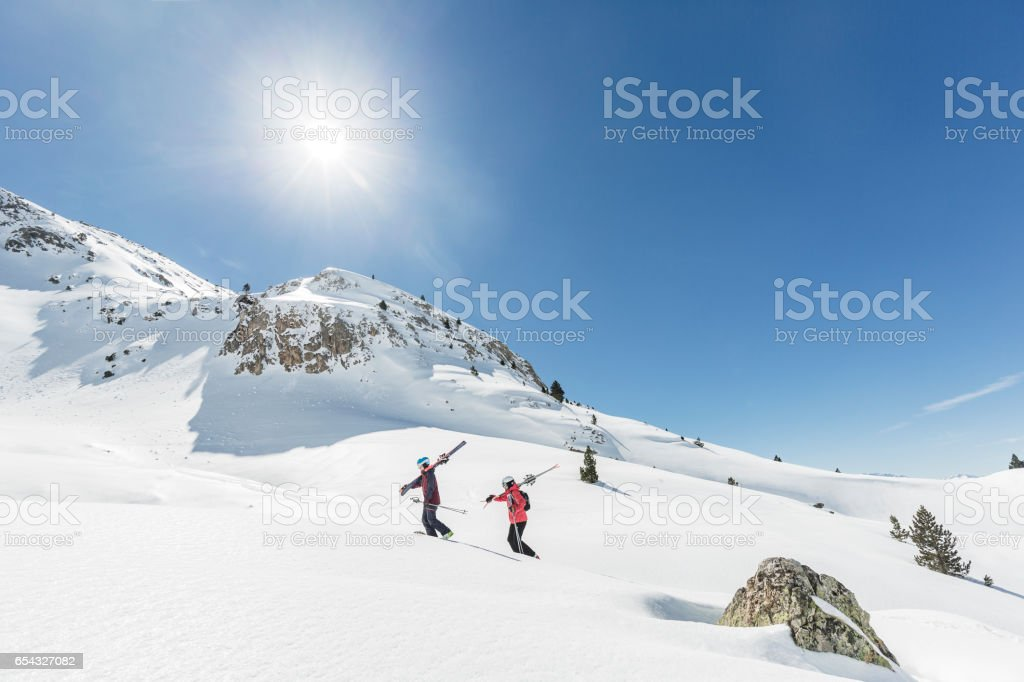 Man and woman backcountry skiers going up the mountain stock photo