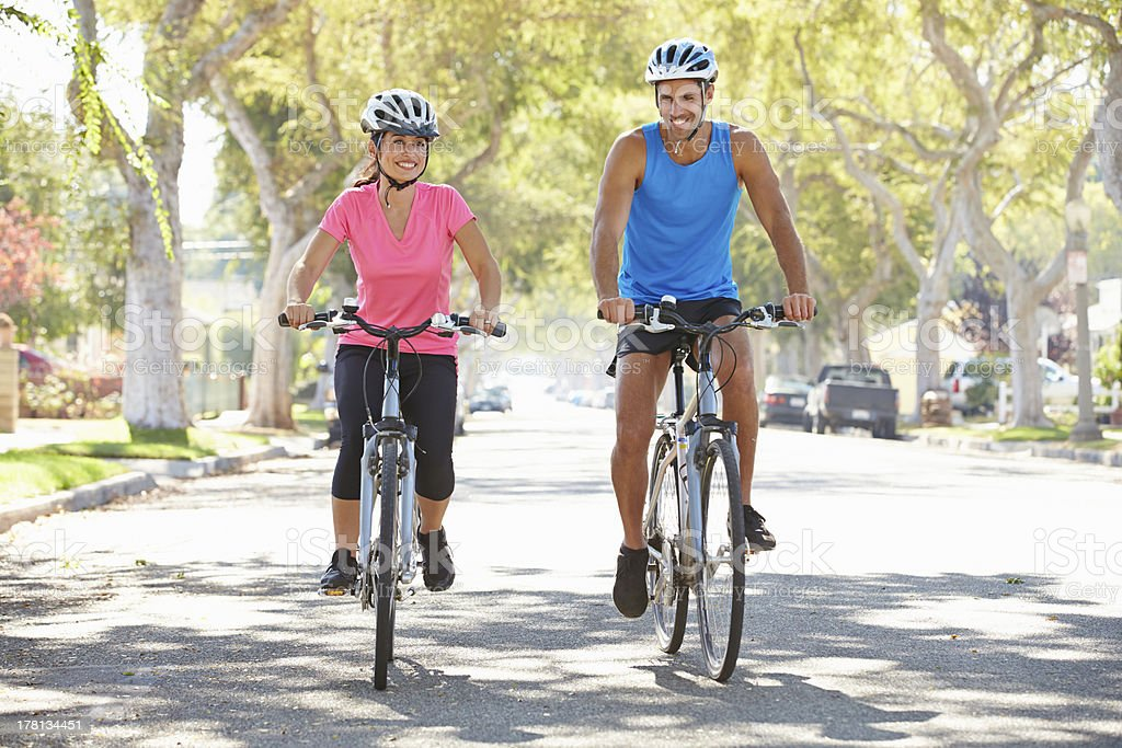 Man and woman bicycling on a suburban street stock photo
