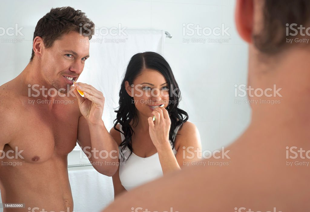 Man and woman brushing their teeth royalty-free stock photo