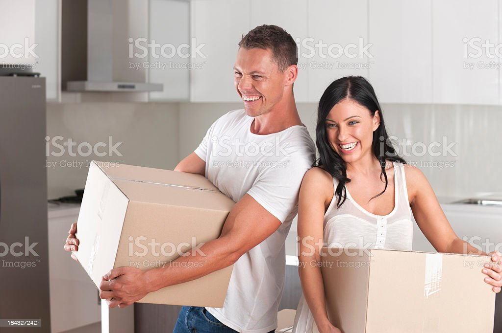 Man and woman carrying moving boxes royalty-free stock photo