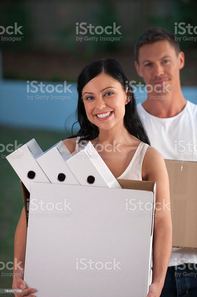 Man and woman carrying office moving boxes stock photo