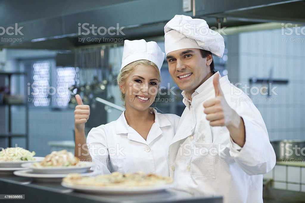 Man and woman chef showing tumbs up. stock photo