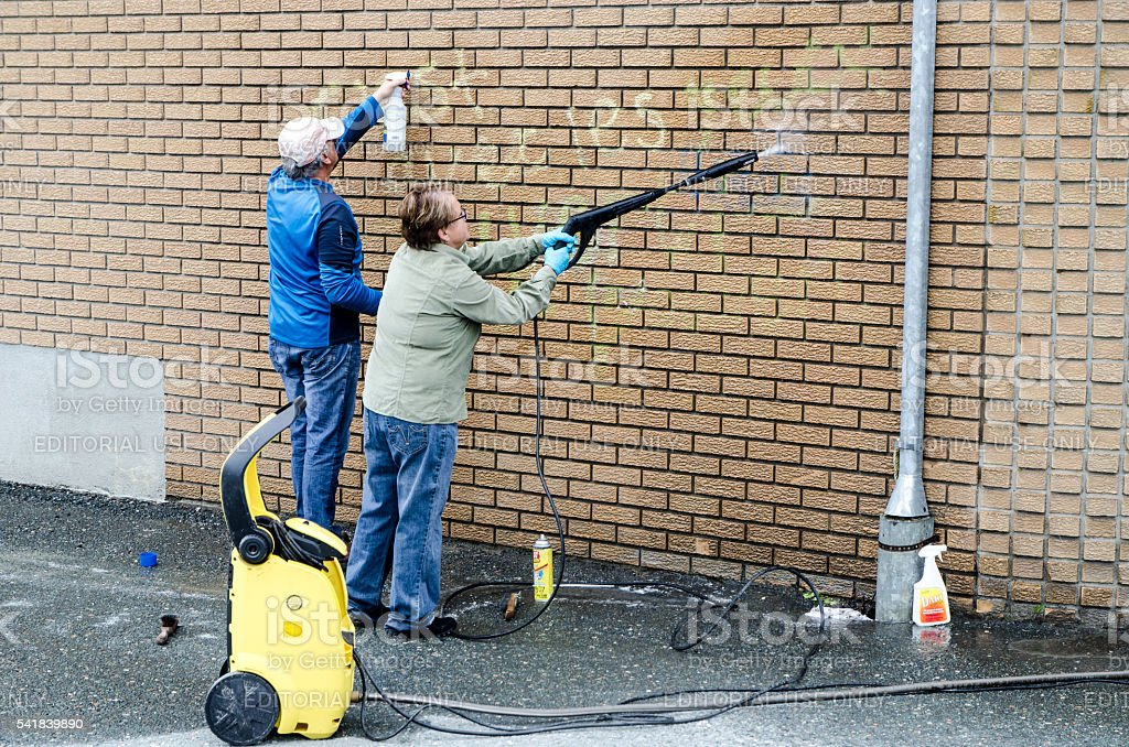 Man and woman cleaning graffiti on their brick wall stock photo