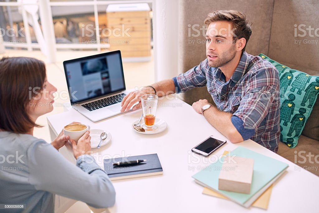 man and woman conducting a business meeting in local cafe stock photo