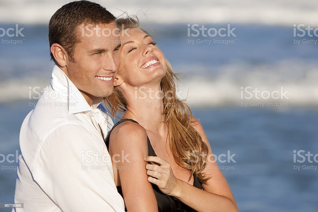 Man and Woman Couple Laughing In Romantic Embrace On Beach royalty-free stock photo