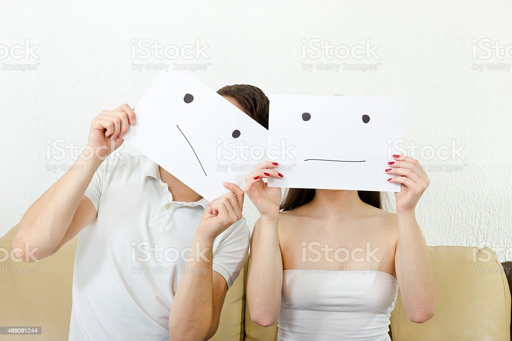 Man and woman cover their faces with sad smile drawn stock photo