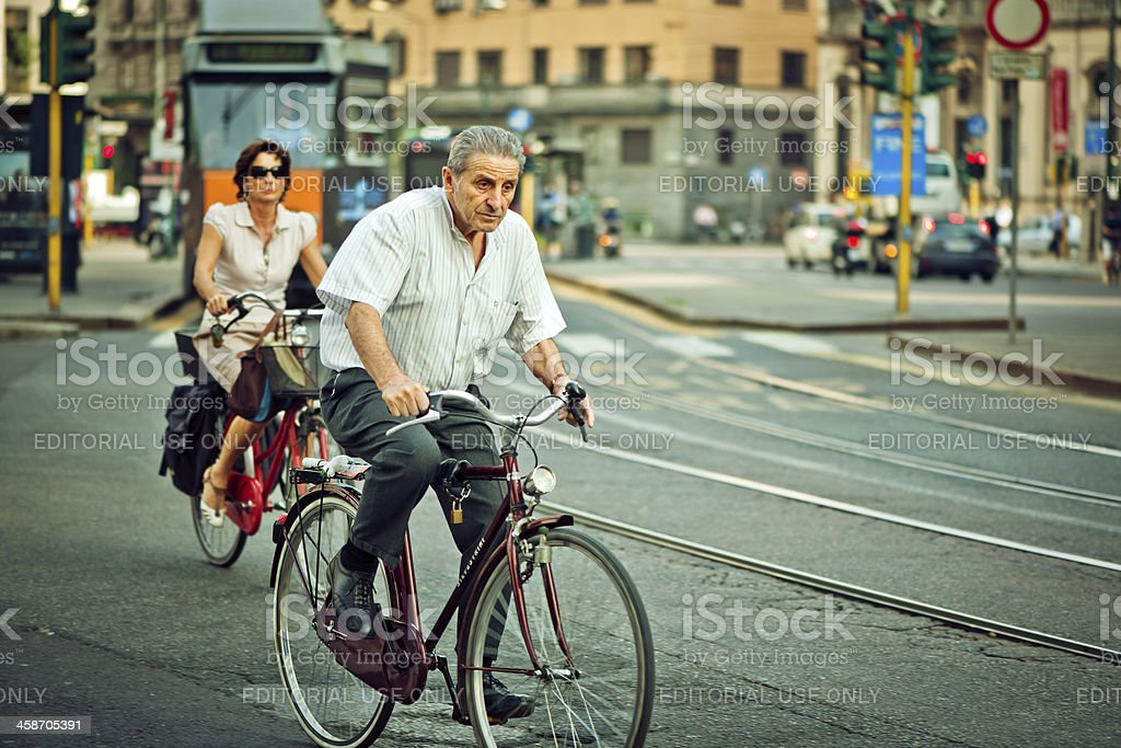 Man and woman cycling in Milan royalty-free stock photo