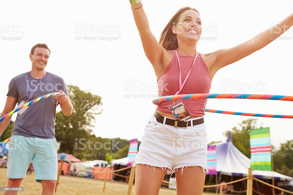 Man and woman dancing with hula hoops at music festival stock photo