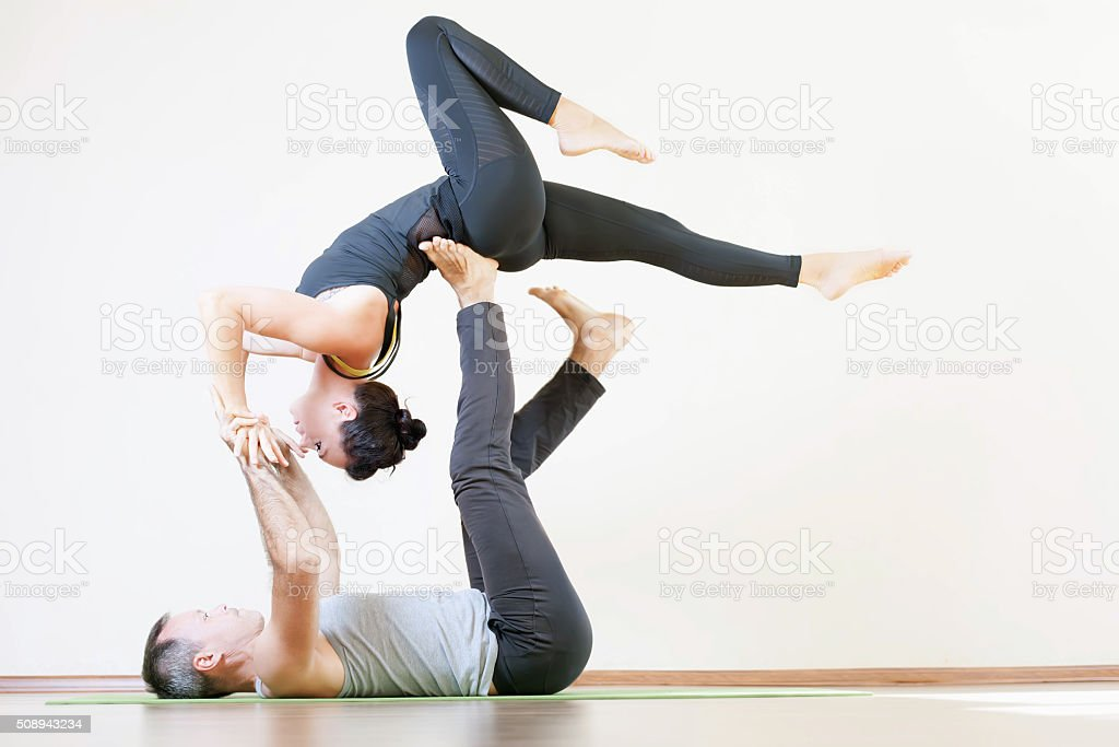 Man and woman doing acro yoga or pair yoga indoor stock photo
