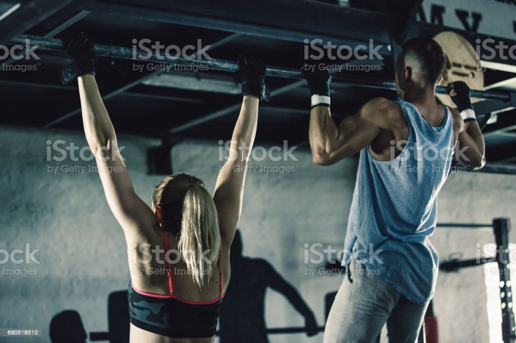 Man and woman doing chin-ups together stock photo