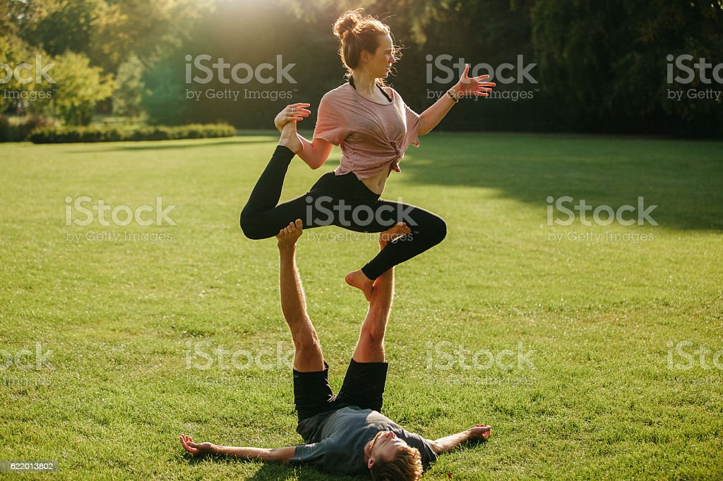 Man and woman doing various yoga poses in pair stock photo