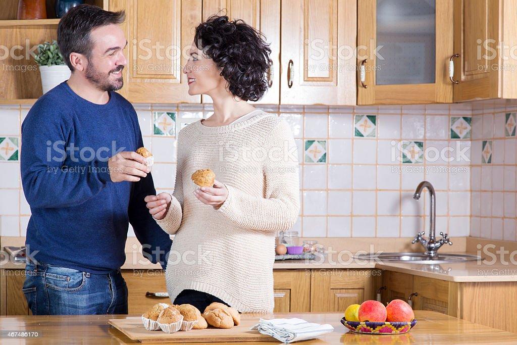 Man and woman eating homemade cupcakes stock photo