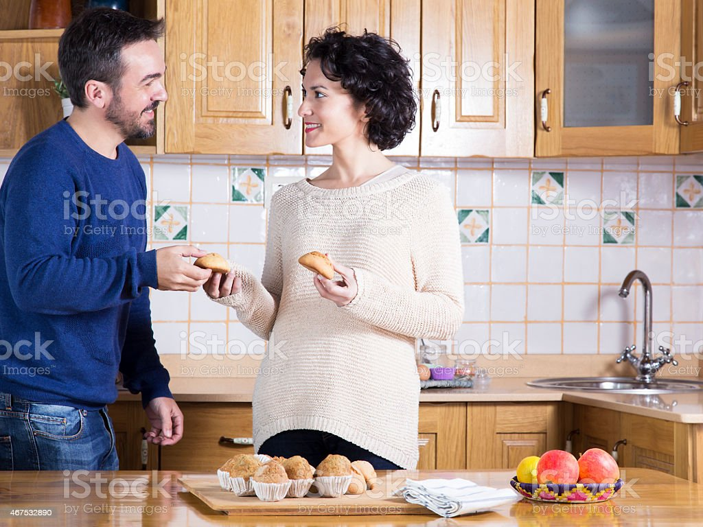 Man and woman eating homemade sweets in the kitchen stock photo