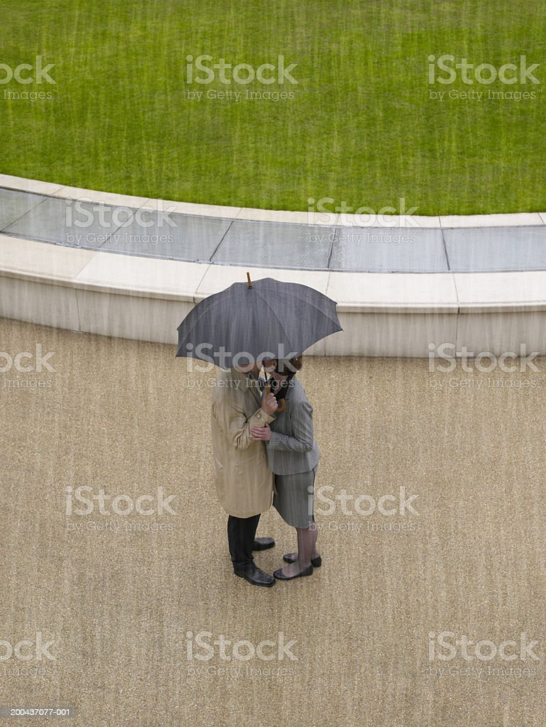 Man and woman embracing under umbrella in rain, overhead view stock photo