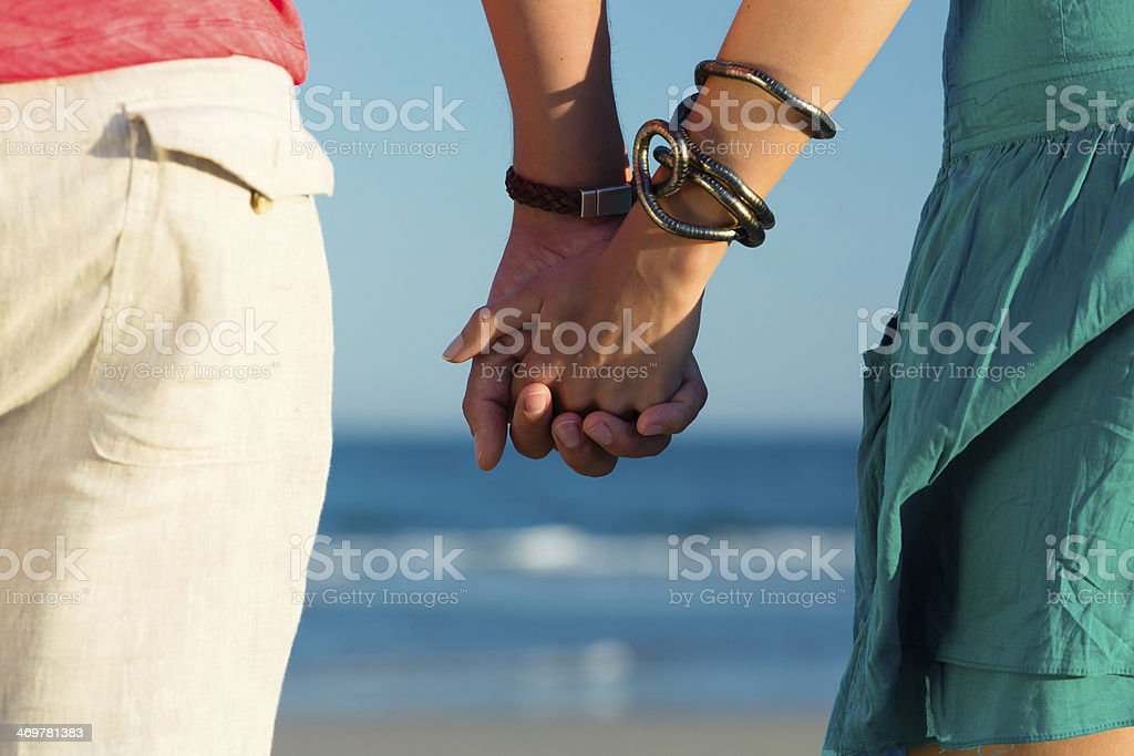 Man and woman enjoying sunset on beach stock photo