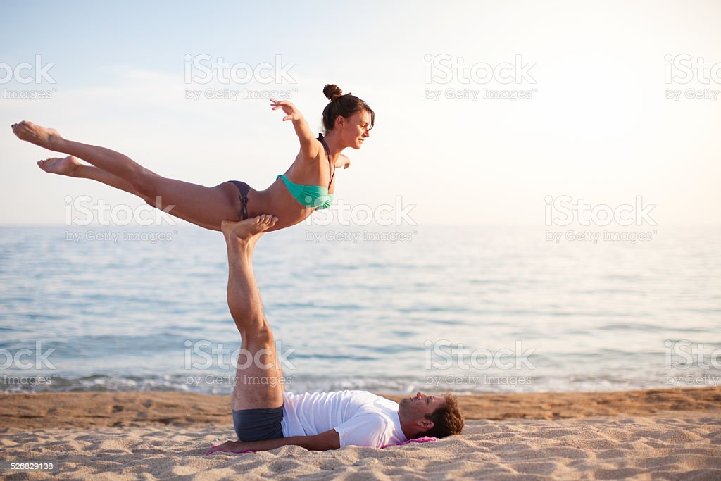 Man and woman exercising on the beach stock photo