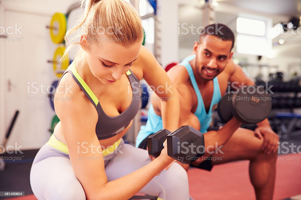 Man and woman exercising with dumbbells at a gym stock photo