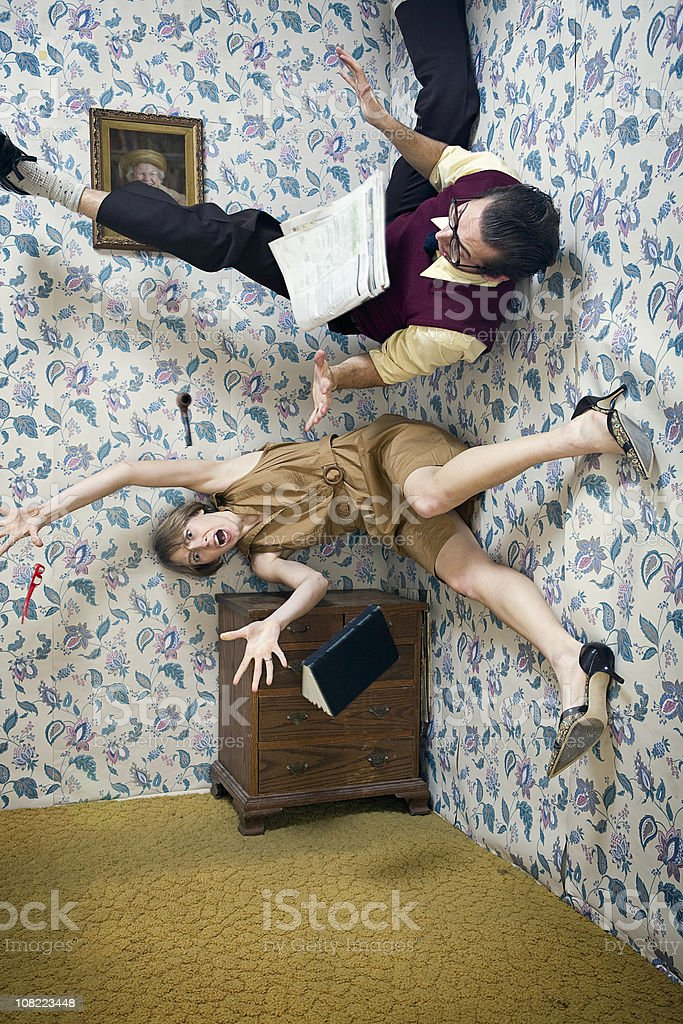 Man and Woman Falling Through The Air in Living Room stock photo