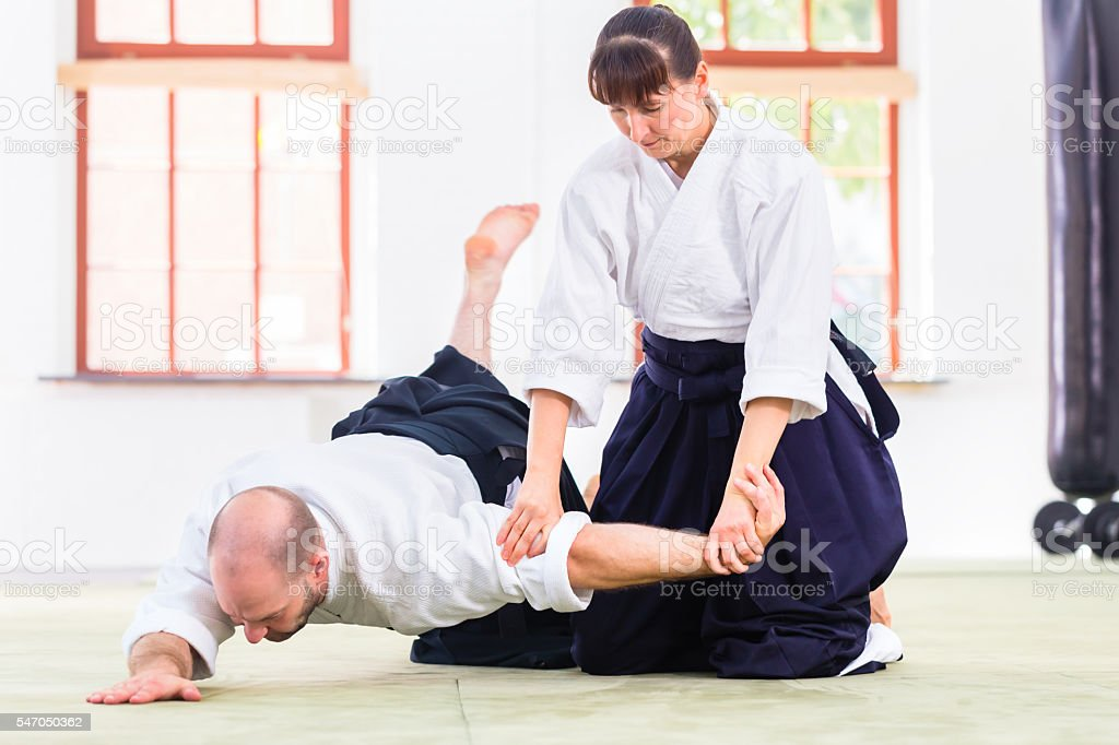 Man and woman fighting at Aikido martial arts school stock photo