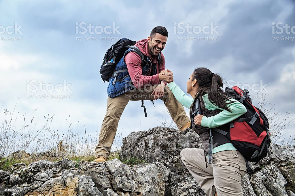 Man and woman help on the rocks stock photo