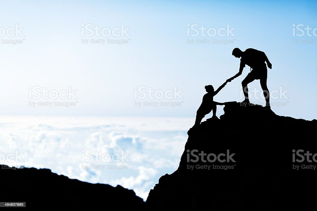Man and woman help silhouette in mountains stock photo