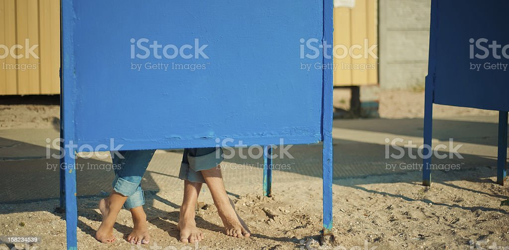 man and woman hiding behind a blue metal curtain stock photo