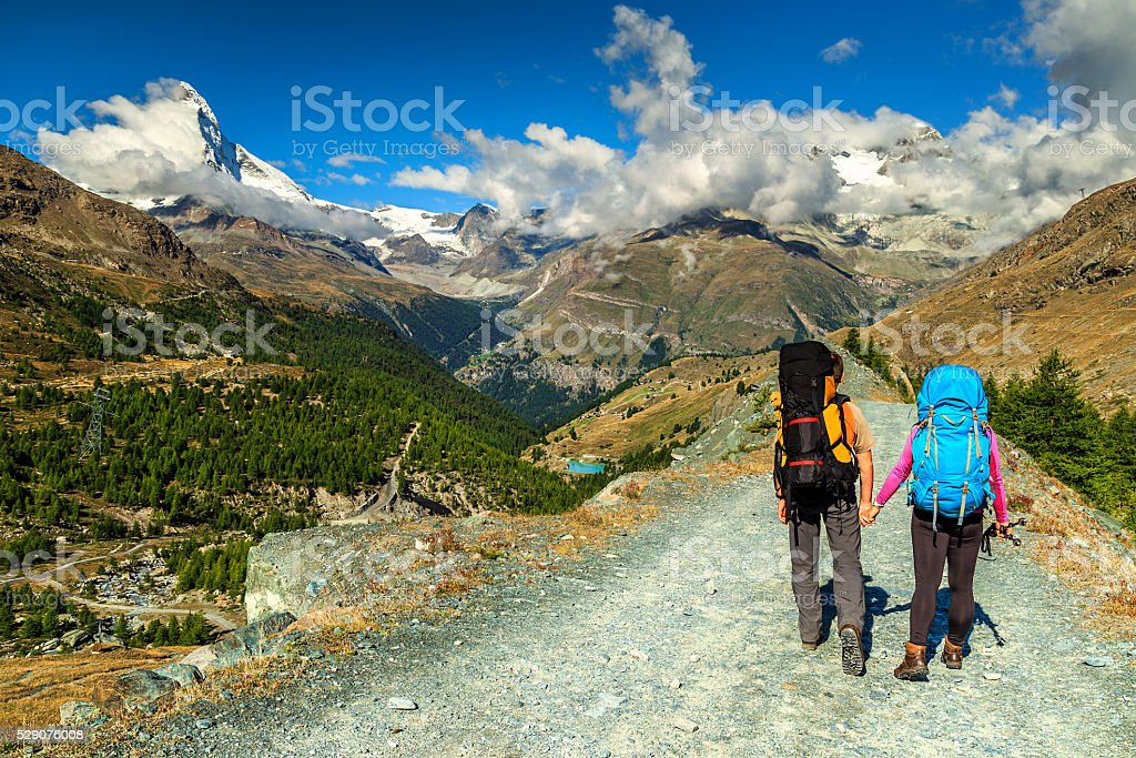 Man and woman hikers trekking in mountains,Valais,Zermatt,Switzerland stock photo